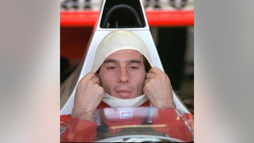 FILE - In this November 4, 1989, file photo, Brazilian driver Ayrton Senna, in a McLaren Honda, pulls on a fire resistant mask before going out to practice for the Australian Grand Prix. Senna won three Formula One titles — in 1988, 1990 and '91 — all with McLaren. He moved to the Williams team for his tragic 1994 season. Despite his career being cut short when he was 34, his 41 wins stand third all-time behind Michael Schumacher's 91 and rival Alain Prost's 51. He died at the 1994 San Marino Grand Prix. (AP Photo/Stephan Holland, File)