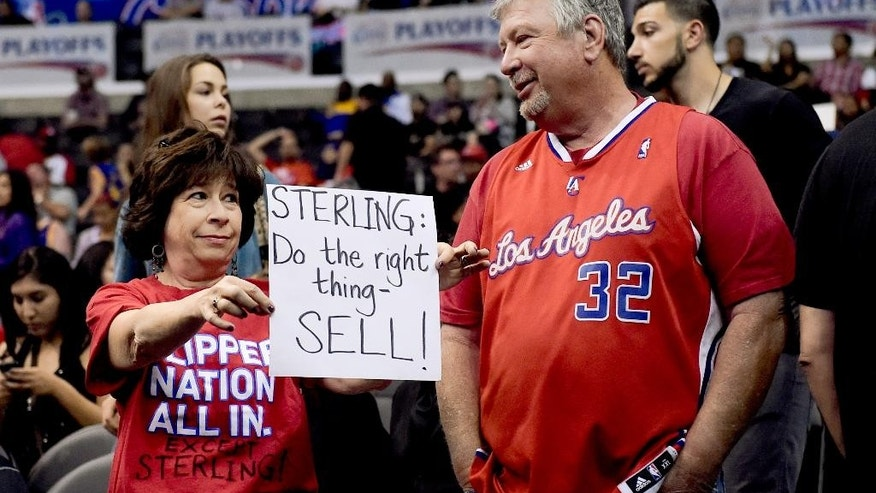 A fan holds up a sign about Los Angeles Clippers owner Donald Sterling before Game 5 of the Clippers' opening-round NBA basketball playoff series against the Golden State Warriors on Tuesday, April 29, 2014, in Los Angeles. NBA Commissioner Adam Silver announced Tuesday that Sterling has been banned for life by the league for making racist comments that hurt the league. (AP Photo)