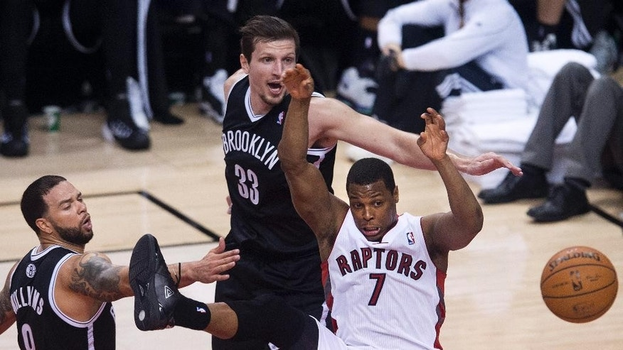 Toronto Raptors guard Kyle Lowry (7) loses control of the ball while driving toward the net past Brooklyn Nets' Mirza Teletovic, center, and Deron Williams, left, during the second half of Game 5 of the opening-round NBA basketball playoff series in Toronto, Wednesday, April 30, 2014. (AP Photo/The Canadian Press, Nathan Denette)