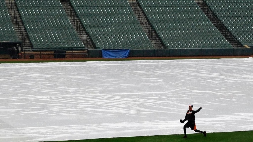 A member of the Baltimore Orioles warms up alongside a tarp covering the infield as rain falls before a scheduled baseball game between the Orioles and the Pittsburgh Pirates, Tuesday, April 29, 2014, in Baltimore. Officials postponed the game due to the rain, and it has been rescheduled for Thursday. (AP Photo/Patrick Semansky)