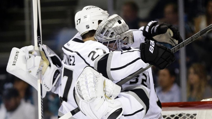 Los Angeles Kings goalie Jonathan Quick, right, celebrates a 5-1 win over the San Jose Sharks with teammate Alec Martinez (27) during Game 7 of an NHL hockey first-round playoff series on Wednesday, April 30, 2014, in San Jose, Calif. (AP Photo/Marcio Jose Sanchez)