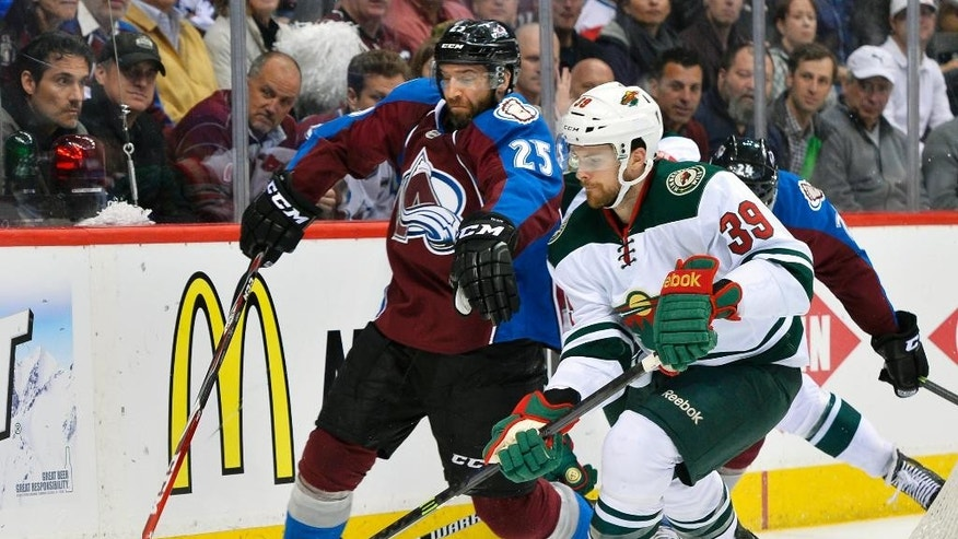 Colorado Avalanche's Maxime Talbot (25) and Minnesota Wild defenseman Nate Prosser (39) chase the puck in the third period during Game 7 of an NHL hockey first-round playoff series on Wednesday, April 30, 2014, in Denver. (AP Photo/Jack Dempsey)