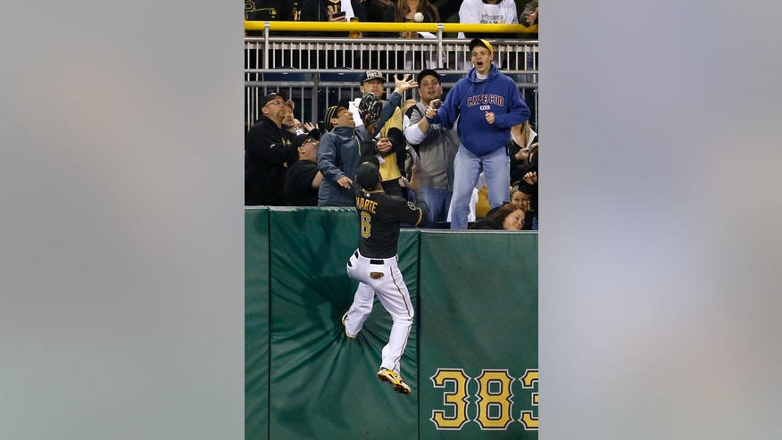 Pittsburgh Pirates left fielder Starling Marte (6) climbs the wall chasing the ball as fans reach for the home run ball hit by Toronto Blue Jays' Colby Rasmus in the fourth inning of a baseball game on Friday, May 2, 2014, in Pittsburgh. (AP Photo/Keith Srakocic)