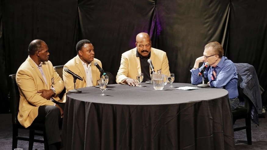 From left: Hall of Famers Harry Carson, Barry Sanders and Jim Brown talk about the road to Canton with moderator Larry King, right, at the inaugural Pro Football Hall of Fame Fan Fest Saturday, May 3, 2014, at the International Exposition Center in Cleveland. (AP Photo/Mark Duncan)