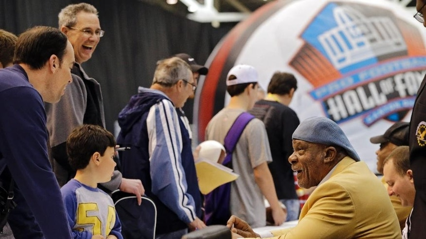 Hall of Fame defensive end Carl Eller, right, signs autographs for fans at the inaugural Pro Football Hall of Fame Fan Fest Saturday, May 3, 2014, at the International Exposition Center in Cleveland. (AP Photo/Mark Duncan)
