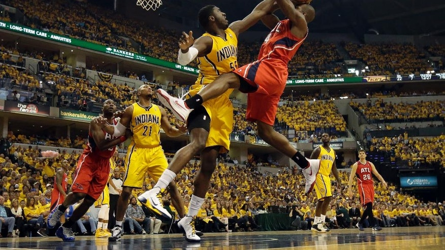 Indiana Pacers center Roy Hibbert, front left, tries to block the shot of Atlanta Hawks forward Paul Millsap during the first half in Game 7 of a first-round NBA basketball playoff series in Indianapolis, Saturday, May 3, 2014. (AP Photo/AJ Mast)