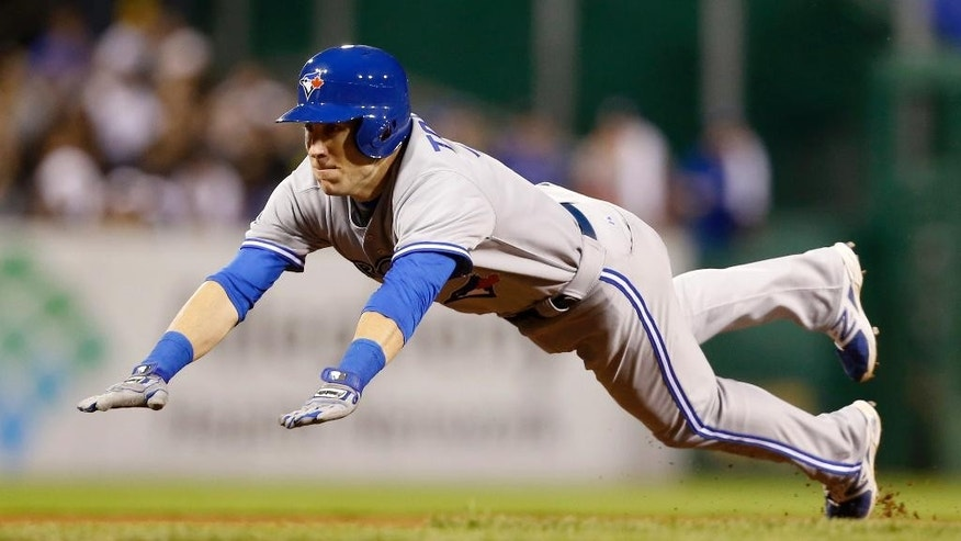 Toronto Blue Jays pinch-hitter Steve Tolleson dives for third with a triple, driving in Brett Lawrie in the sixth inning of the baseball game against the Pittsburgh Pirates on Friday, May 2, 2014, in Pittsburgh. (AP Photo/Keith Srakocic)