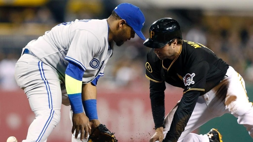 The ball gets past Toronto Blue Jays third baseman Juan Francisco as Pittsburgh Pirates' Neil Walker, right, takes third on a wild pitch in the fifth inning of the baseball game on Friday, May 2, 2014, in Pittsburgh. (AP Photo/Keith Srakocic)