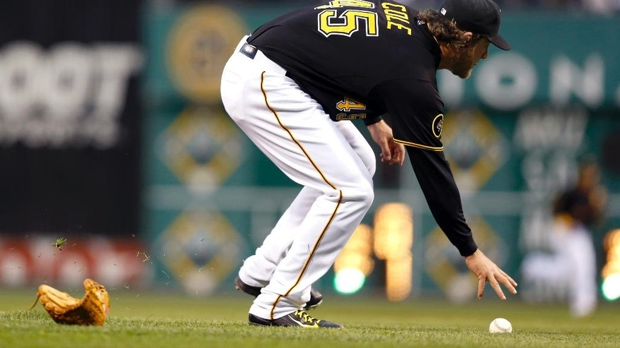 Pittsburgh Pirates starting pitcher Gerrit Cole reaches for the ball after a line drive by Toronto Blue Jays' Jose Bautista knocked his glove off in the third inning of the baseball game on Friday, May 2, 2014, in Pittsburgh. Cole made the  throw to first and Bautista was out. (AP Photo/Keith Srakocic)