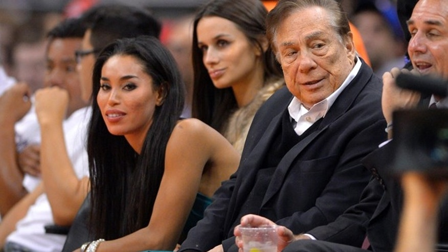 Los Angeles Clippers owner Donald Sterling, right, and V. Stiviano, left, watch the Clippers play the Sacramento Kings. (AP)