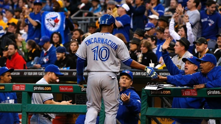 Toronto Blue Jays' Edwin Encarnacion (10) returns to the dugout after scoring on a single by Jays' Colby Rasmus off Pittsburgh Pirates starting pitcher Francisco Liriano during the fourth inning of a baseball game in Pittsburgh, Saturday, May 3, 2014. (AP Photo/Gene J. Puskar)