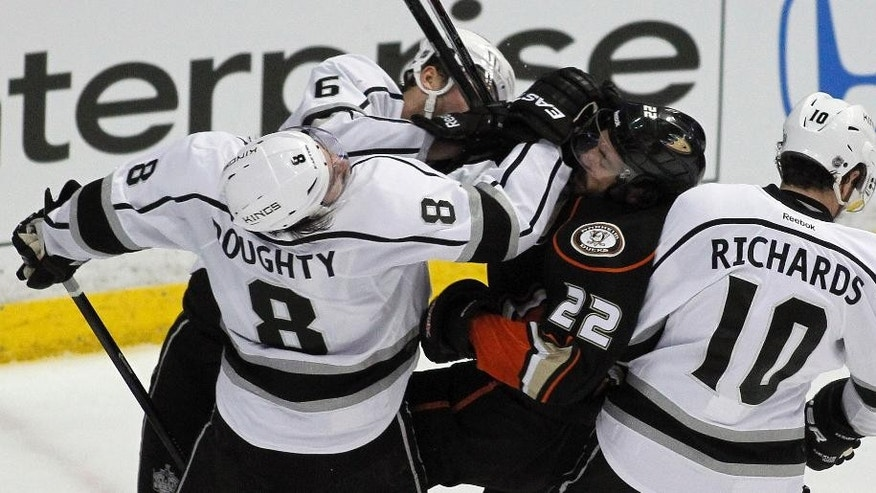 Anaheim Ducks center Mathieu Perreault (22) gets hit by Los Angeles Kings defenseman Jake Muzzin (6), defenseman Drew Doughty (8), and center Mike Richards (10) during the second period in Game 1 of an NHL hockey second-round Stanley Cup playoff series in Anaheim, Calif., Saturday, May 3, 2014. (AP Photo/Alex Gallardo)