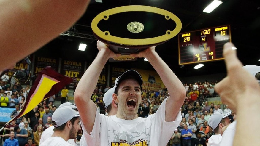 Loyola's Cody Caldwell (12), center, celebrates as he holds the championship trophy after his team defeated Stanford 3-1 in the NCAA men's college volleyball championship at Gentile Arena in Chicago on Saturday, May 3, 2014. (AP Photo/Nam Y. Huh)