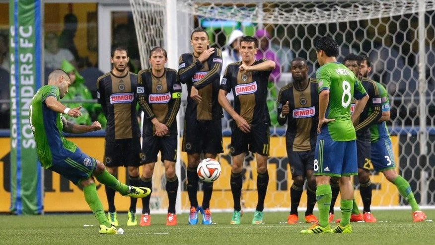 Philadelphia Union players make a wall as Seattle Sounders' Clint Dempsey, left, takes a penalty kick in the first half of an MLS soccer match, Saturday, May 3, 2014, in Seattle. The kick went wide to the right.(AP Photo/Ted S. Warren)