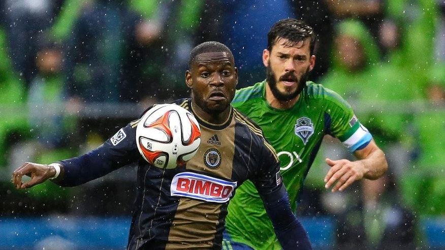 As rain flls, Philadelphia Union's Maurice Edu, left, and Seattle Sounders' Brad Evans, right, battle for the ball in the first half of an MLS soccer match, Saturday, May 3, 2014, in Seattle. (AP Photo/Ted S. Warren)