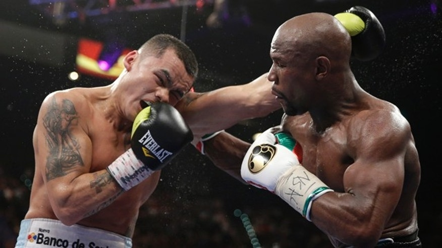 May 3, 2014: Marcos Maidana, left, from Argentina, trades blows with Floyd Mayweather Jr. in their WBC-WBA welterweight title boxing fight in Las Vegas. Mayweather won the bout by majority decision. (AP Photo/Isaac Brekken)