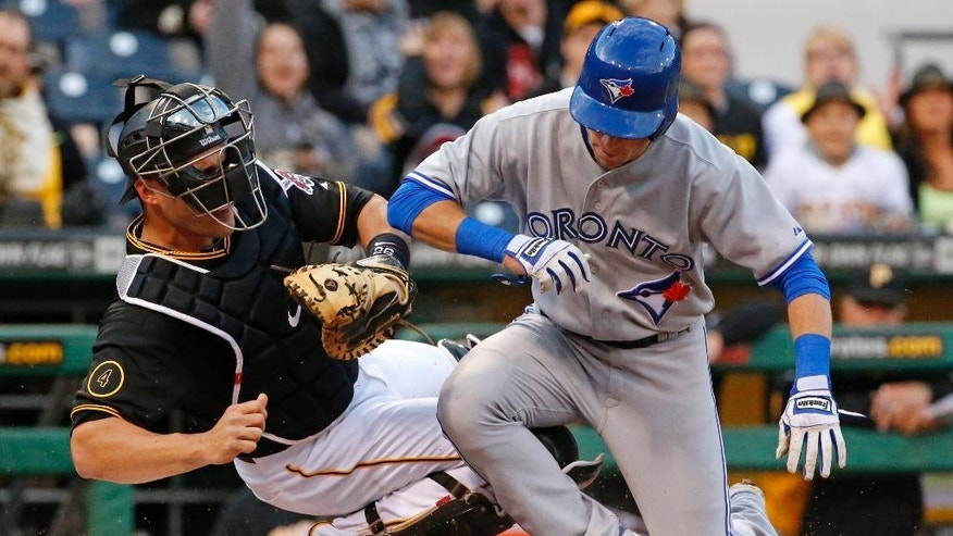 Toronto Blue Jays' Steve Tolleson, right, is tagged out by Pittsburgh Pirates catcher Tony Sanchez during the third inning of a baseball game in Pittsburgh, Saturday, May 3, 2014. Tolleson was attempting to score on a single by Josh Thole. (AP Photo/Gene J. Puskar)