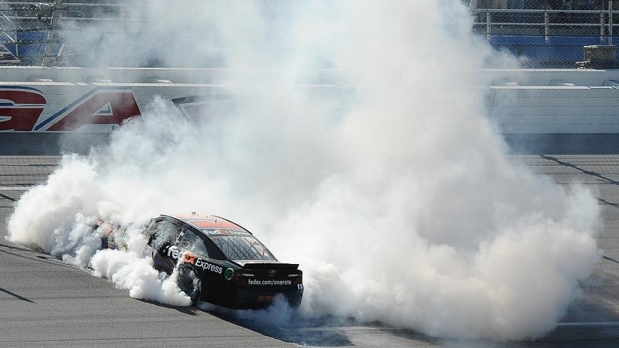 Denny Hamlin (11) does a celebratory burnout after winning the NASCAR Aaron's 499 Sprint Cup series auto race under caution at Talladega Superspeedway, Sunday, May 4, 2014, in Talladega, Ala. (AP Photo/Rainier Ehrhardt)
