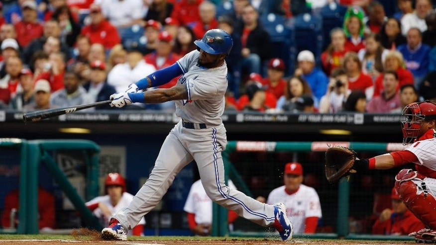 Toronto Blue Jays' Jose Reyes, left, hits a home run off Philadelphia Phillies starting pitcher Kyle Kendrick as catcher Carlos Ruiz looks on during the first inning of an interleague baseball game, Monday, May 5, 2014, in Philadelphia. (AP Photo/Matt Slocum)