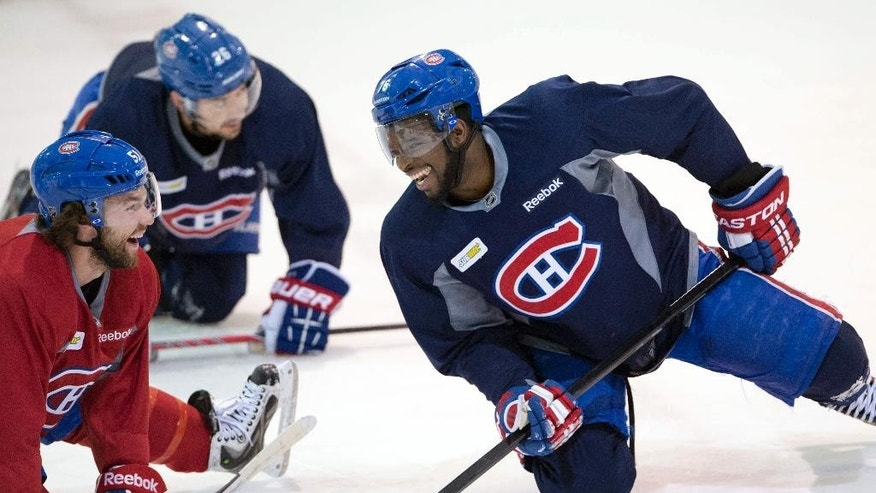 Montreal Canadiens defenceman P.K. Subban, right, has a laugh with teammate David Desharnais during the NHL hockey team's practice session Monday, May 5, 2014, in Brossard, Quebec. The Canadiens play the Boston Bruins in Game 3 of the second round of the Stanley Cup playoffs Tuesday in Montreal.  (AP Photo/The Canadian Press, Ryan Remiorz)