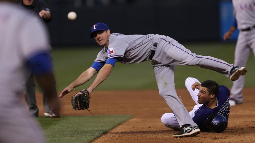 Texas Rangers second baseman Josh Wilson, back top, flies over Colorado Rockies' Nelson Arenado to throw to first baseman Prince Fielder after tagging out Arenado on the front end of a double play that ended the third inning of an interleague baseball game in Denver on Monday, May 5, 2014. (AP Photo/David Zalubowski)