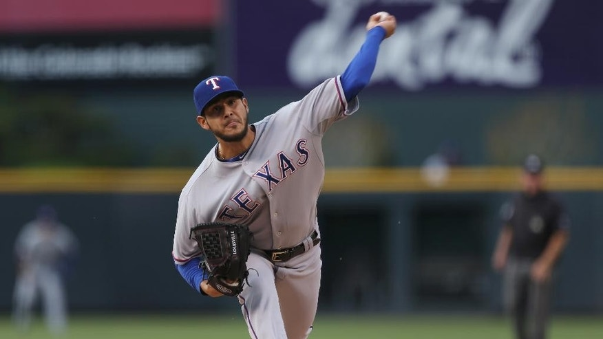 Texas Rangers starting pitcher Martin Perez works against the Colorado Rockies in the first inning of an interleague baseball game in Denver on Monday, May 5, 2014. (AP Photo/David Zalubowski)