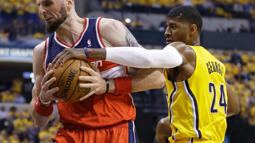 Washington Wizards' Marcin Gortat (4) is defended by Indiana Pacers' Paul George (24) during the first quarter of game 1 of the Eastern Conference semifinal NBA basketball playoff series in Indianapolis, Monday, May 5, 2014(AP Photo/Michael Conroy)