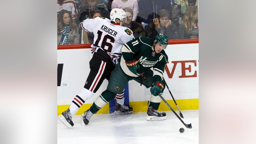 Minnesota Wild left wing Zach Parise (11) controls the puck in front of Chicago Blackhawks center Marcus Kruger (16) during the first period of Game 3 of an NHL hockey second-round playoff series in St. Paul, Minn., Tuesday, May 6, 2014. (AP Photo/Ann Heisenfelt)