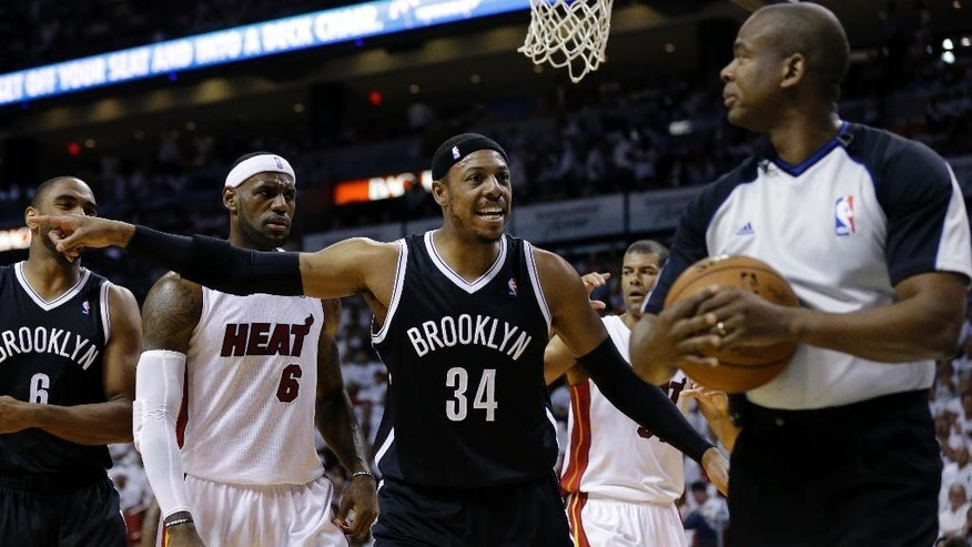 Brooklyn Nets' Paul Pierce (34) reacts to a call by official Sean Wright, right, as Miami Heat's LeBron James (6) looks on in the first half of Game 1 in an NBA Eastern Conference semifinal basketball game, Tuesday, May 6, 2014, in Miami.  (AP Photo/Lynne Sladky)
