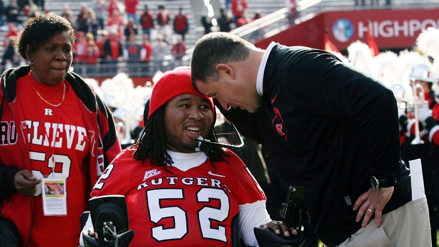Nov. 19, 2011: In this file photo, paralyzed former Rutgers football player Eric LeGrand, center, is greeted by coach Greg Schiano, right, before an NCAA college football game against Cincinnati in Piscataway, N.J.