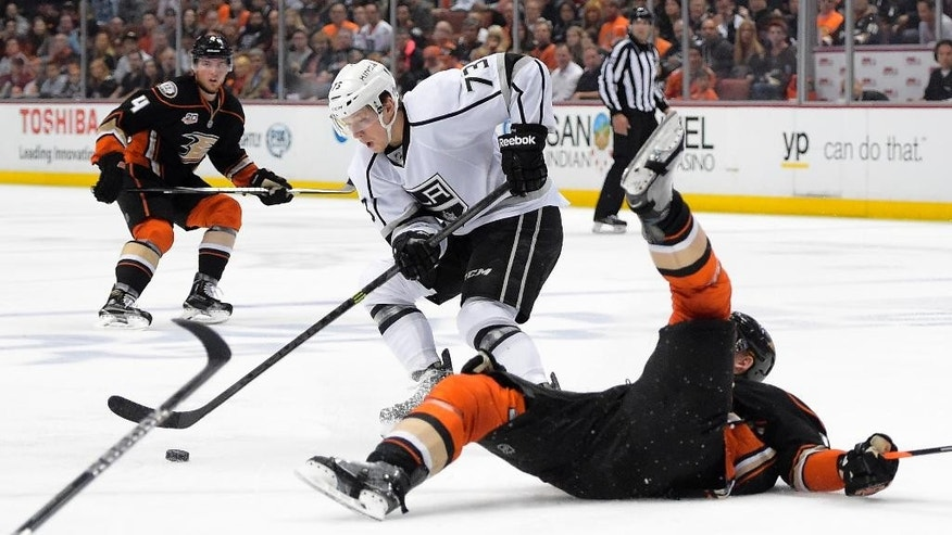 Anaheim Ducks right wing Corey Perry, right, falls as Los Angeles Kings center Tyler Toffoli, center, takes the puck while Ducks defenseman Cam Fowler looks on during the second period in Game 2 of an NHL hockey second-round Stanley Cup playoff series, Monday, May 5, 2014, in Anaheim, Calif.  (AP Photo/Mark J. Terrill)