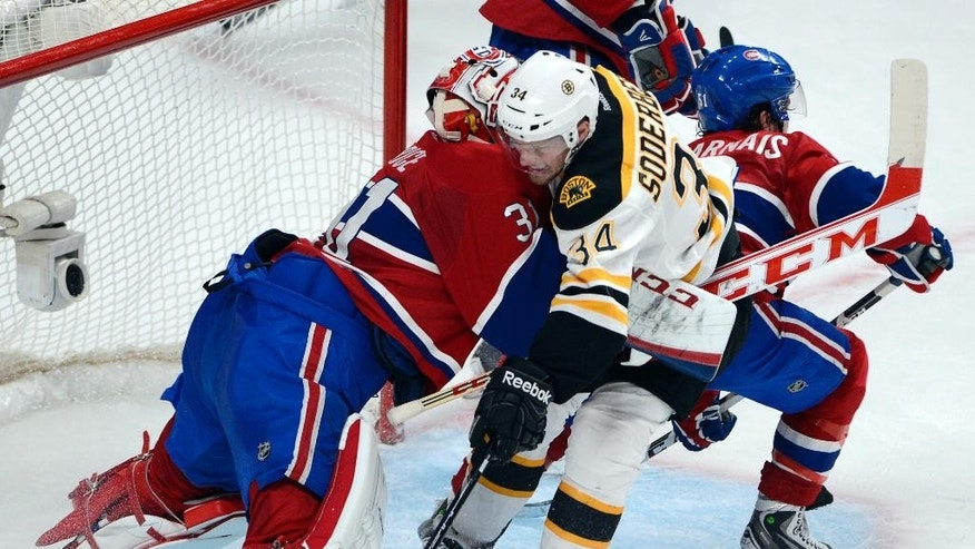 Boston Bruins center Carl Soderberg (34) is sandwiched between Montreal Canadiens goalie Carey Price (31) and center David Desharnais (51) during the second period of Game 3 of an NHL hockey Stanley Cup playoff series, Tuesday, May 6, 2014, in Montreal. (AP Photo/The Canadian Press, Ryan Remiorz)
