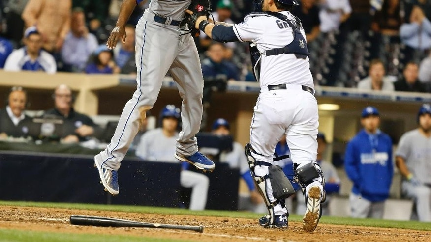 San Diego Padres catcher Yasmani Grandal puts tag on Kansas City Royals' Lorenzo Cain who is out trying to score from third on an infield grounder in the 11th inning of a baseball game Monday, May 5, 2014, in San Diego.  (AP Photo/Lenny Ignelzi)