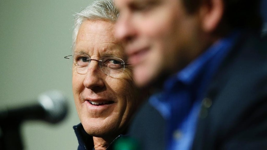 Seattle Seahawks head coach Pete Carroll, left, looks at general manager John Schneider, right, as they talk to reporters, Tuesday, May 6, 2014, in Renton, Wash., about the upcoming NFL football draft. (AP Photo/Ted S. Warren)