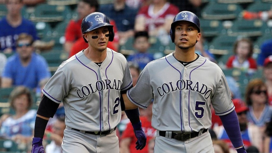 Colorado Rockies' Troy Tulowitzki (2) and Carlos Gonzalez (5) congratulate each other after scoring on a Nolan Arenado double in the first inning of a baseball game against the Texas Rangers, Wednesday, May 7, 2014, in Arlington, Texas. (AP Photo/Tony Gutierrez)
