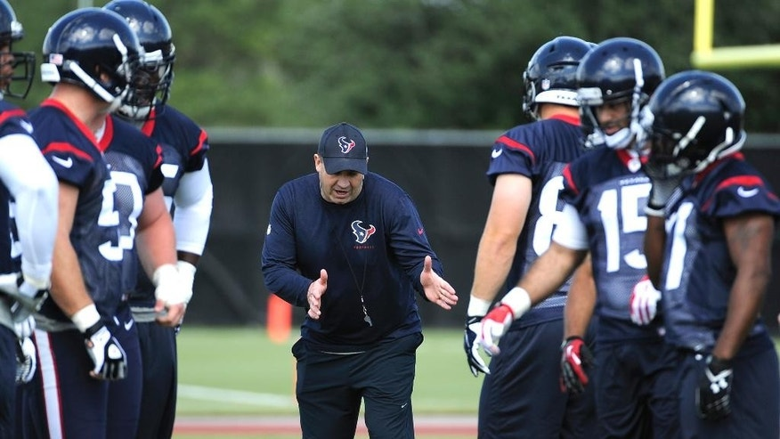 New Houston Texans coach Bill O'Brien, center, works with players during a voluntary veteran NFL football minicamp, Tuesday, May 6, 2014, in Houston. He takes over a team that was expected to contend for a Super Bowl but instead fell to a league-worst 2-14 last season. (AP Photo/Pat Sullivan)