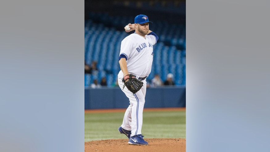 Toronto Blue Jays pitcher Mark Buehrle tries to pick off Philadelphia Phillies' Cody Asche at first during third inning interleague baseball action in Toronto on Wednesday May 7, 2014. (AP Photo/The Canadian Press, Chris Young)