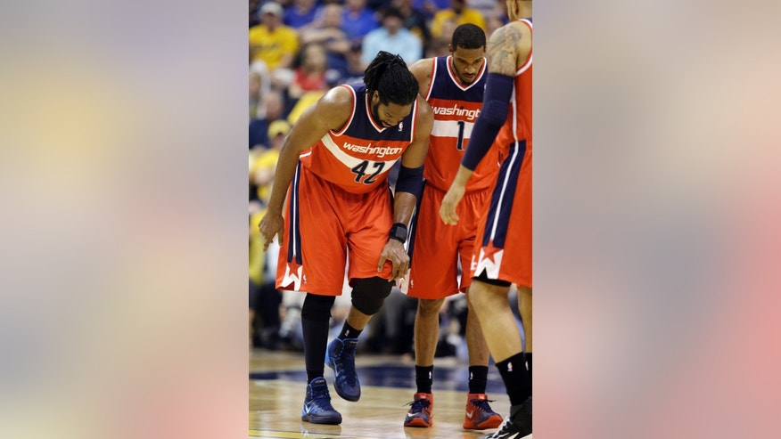 Washington Wizards forward Nene Hilario, left, holds his knee next to teammate Trevor Ariza after he was hurt during the first half of game 2 of the Eastern Conference semifinal NBA basketball playoff series against the Indiana Pacers on Wednesday, May 7, 2014, in Indianapolis. (AP Photo/Darron Cummings)