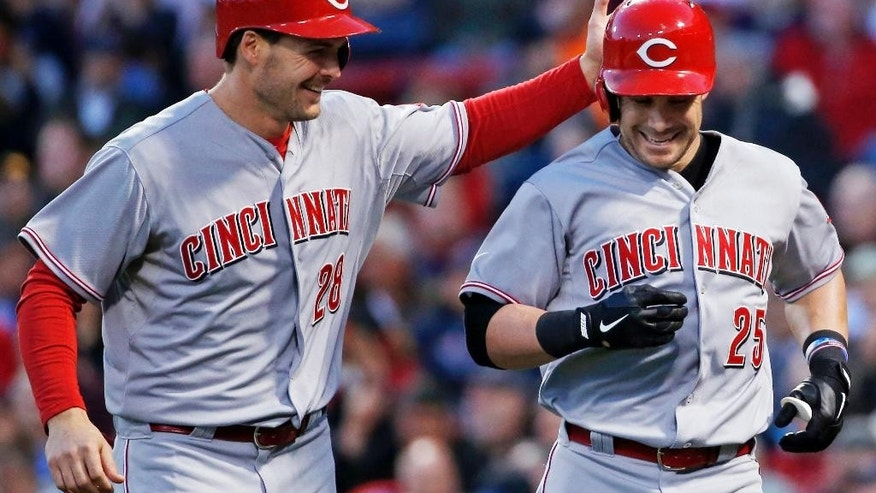 Cincinnati Reds' Skip Schumaker (25) is congratulated by Chris Heisey (28) after his two-run homer against the Boston Red Sox during the third inning of a baseball game at Fenway Park in Boston, Wednesday, May 7, 2014. (AP Photo/Elise Amendola)