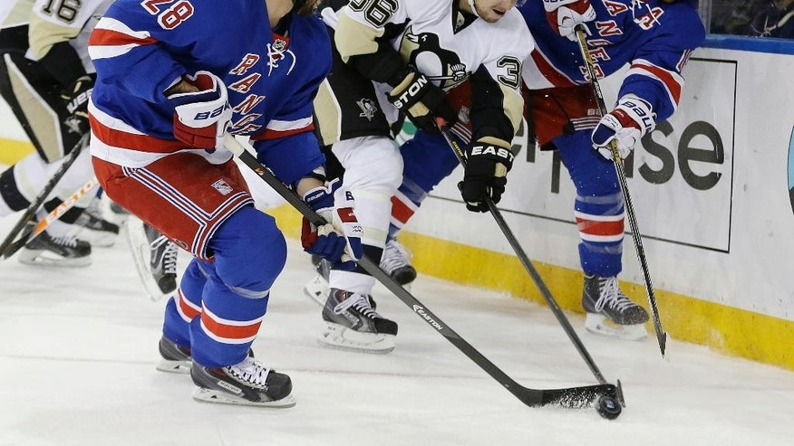 Pittsburgh Penguins' Jussi Jokinen (36), of Finland, fights for control of the puck with New York Rangers' Dominic Moore (28) and Marc Staal (18) during the first period of a second-round NHL Stanley Cup hockey playoff series Wednesday, May 7, 2014, in New York. (AP Photo/Frank Franklin II)