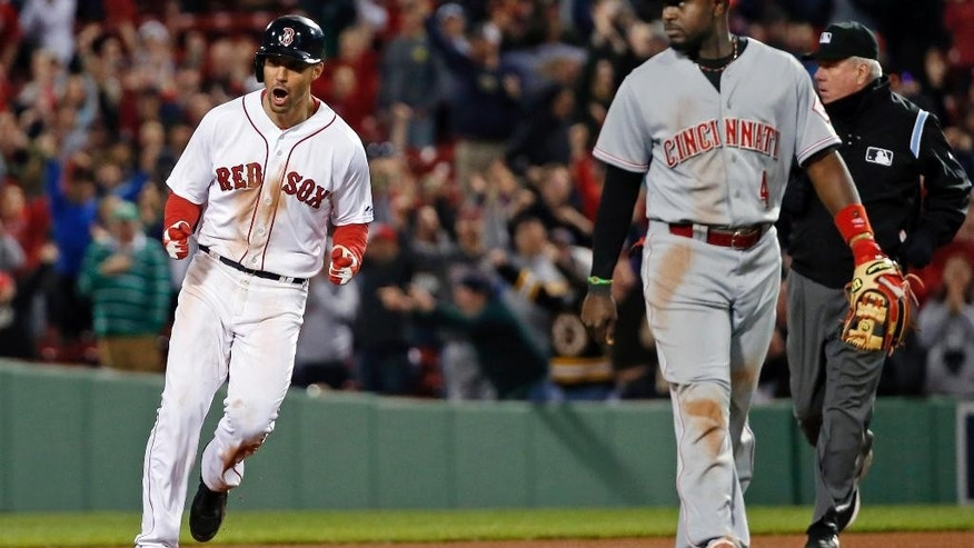 Boston Red Sox's Grady Sizemore, left, celebrates his walk-off single to defeat the Cincinnati Reds 4-3 in the 12th inning of a baseball game at Fenway Park in Boston, Tuesday, May 6, 2014. Watching at right is Reds second baseman Brandon Phillips. (AP Photo/Elise Amendola)