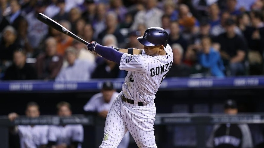 Colorado Rockies' Carlos Gonzalez follows through with his swing after connecting for an RBI-single against the Texas Rangers in the sixth inning of an interleague baseball game in Denver on Tuesday, May 6, 2014. (AP Photo/David Zalubowski)
