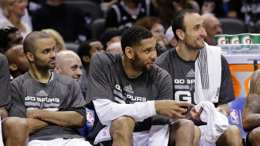 San Antonio Spurs' Tony Parker, left, of France, Tim Duncan, center, and Manu Ginobili, right, sit on the bench during the second half of Game 1 of a Western Conference semifinal NBA basketball playoff series against the Portland Trail Blazers, Tuesday, May 6, 2014, in San Antonio. San Antonio won 116-92. (AP Photo/Eric Gay)