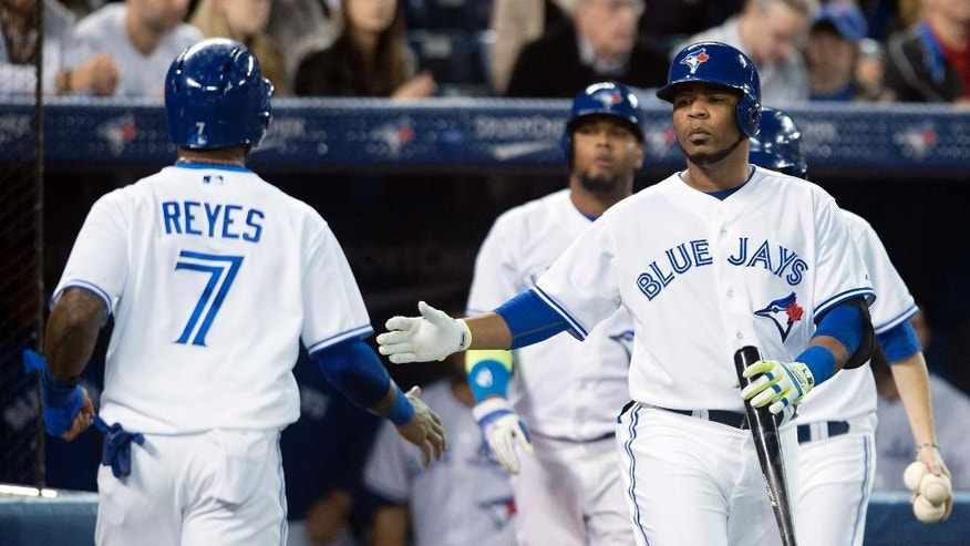 Toronto Blue Jays' Edwin Encarnacion, right, and Jose Reyes celebrate after Reyes scored in the third inning of a baseball game against the Philadelphia Phillies in Toronto on Thursday, May 8, 2014. (AP Photo/The Canadian Press, Darren Calabrese)