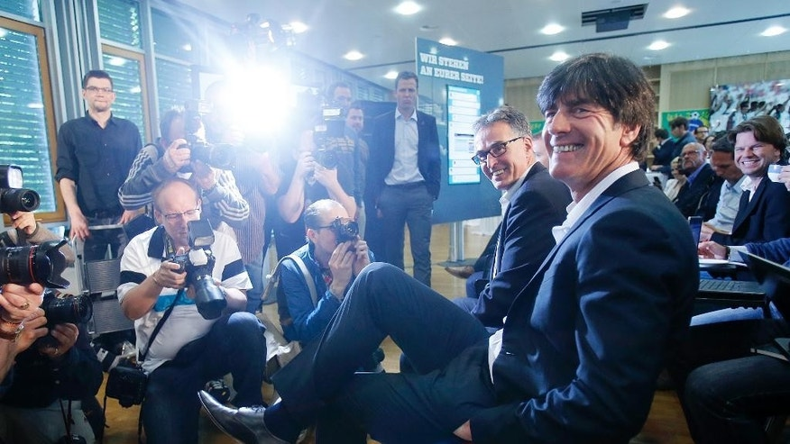 Joachim Loew, the coach of German national soccer team, smiles as he waits for the beginning of a press conference where he presented his preliminary team for the upcoming World Cup in Brazil in Frankfurt, Germany, Thursday, May 8, 2014. (AP Photo/Michael Probst)
