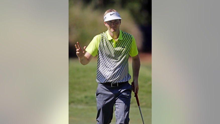Russell Henley raises his hand after making par on the eighth hole during the first round of The Players championship golf tournament at TPC Sawgrass, Thursday, May 8, 2014 in Ponte Vedra Beach, Fla. (AP Photo/Gerald Herbert)