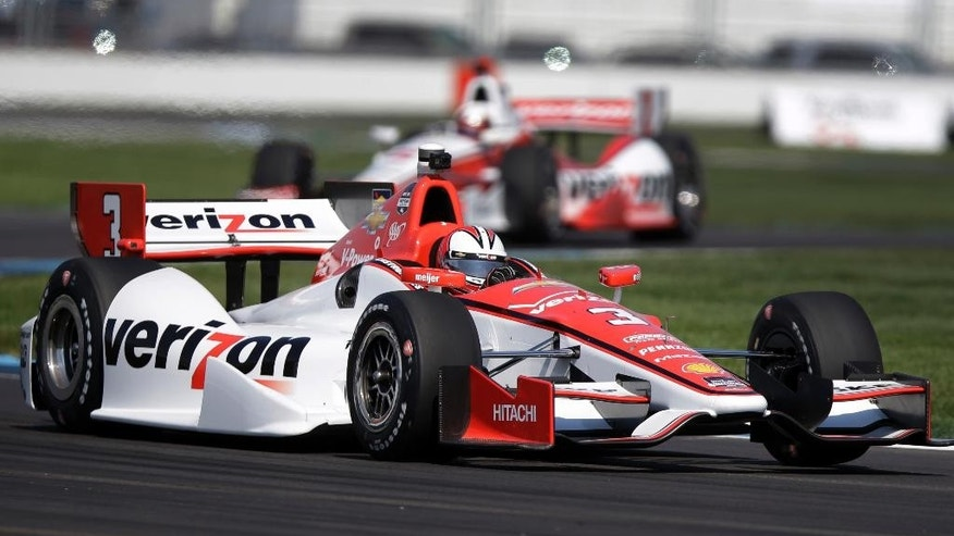 Helio Castroneves, of Brazil, leads teammate Juan Pablo Montoya, of Colombia, through turn 7 during practice for the inaugural Grand Prix of Indianapolis IndyCar auto race at the Indianapolis Motor Speedway in Indianapolis, Thursday, May 8, 2014. (AP Photo/Michael Conroy)