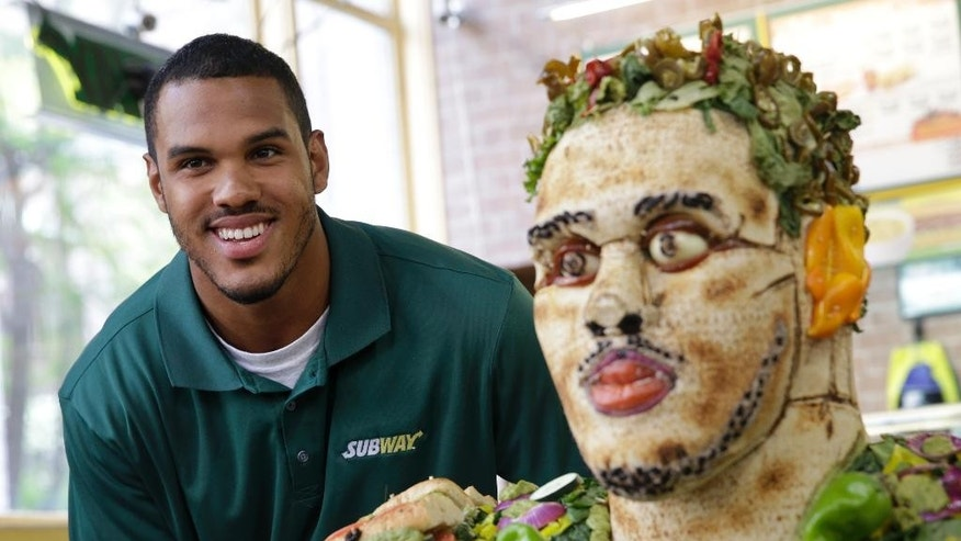 2014 draft prospect Anthony Barr poses for a picture with a food sculpture of himself at a Subway restaurant in New York, Wednesday, May 7, 2014. (AP Photo/Seth Wenig)