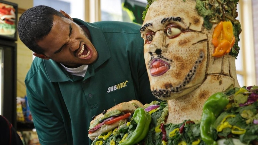 2014 draft prospect Anthony Barr pretends to eat a sculpture of himself made of food at a Subway restaurant in New York, Wednesday, May 7, 2014. (AP Photo/Seth Wenig)