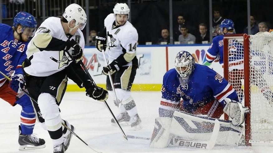 Pittsburgh Penguins' Evgeni Malkin, second from left, of Russia, shoots the puck past New York Rangers' Henrik Lundqvist (30), of Sweden, during the first period of their second-round NHL Stanley Cup hockey playoff series Wednesday, May 7, 2014, in New York. (AP Photo/Frank Franklin II)